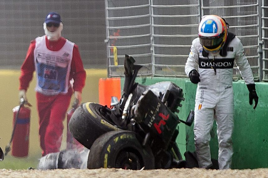 Fernando Alonso walking past the mangled wreck of his McLaren after he collided with Haas' Esteban Gutierrez on the 18th lap of the Australian GP yesterday. His car hit a barrier before it rolled and flew end-over-end into a second barrier. The race