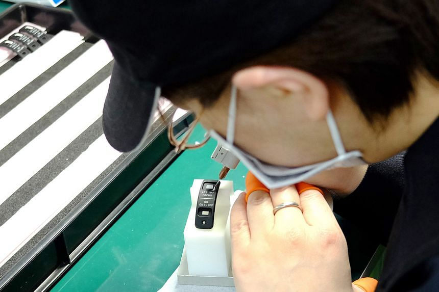 A Sigma worker inspecting a polished lens element (above) at the company's Aizu factory in Japan. The painstaking work (left) of painting the markings of a len's side switch. Nearly 80 per cent of Sigma's 1,800-strong workforce are engineers.