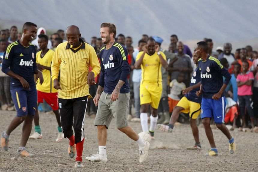 After playing football with students in Nepal, his face is covered with crimson paint, the national colour of Nepal. David Beckham poses with the children in Kumnga village (above) after an impromptu football match in the rain in Papua New Guinea, an
