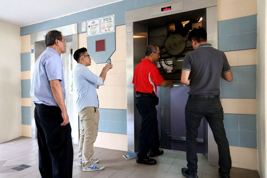 Repairmen inspecting a lift at Block 322, Tah Ching Road, last October after a resident's hand was severed when the doors of the lift closed before her dog could enter, and while its leash was looped around her left wrist. As the lift moved up, her h
