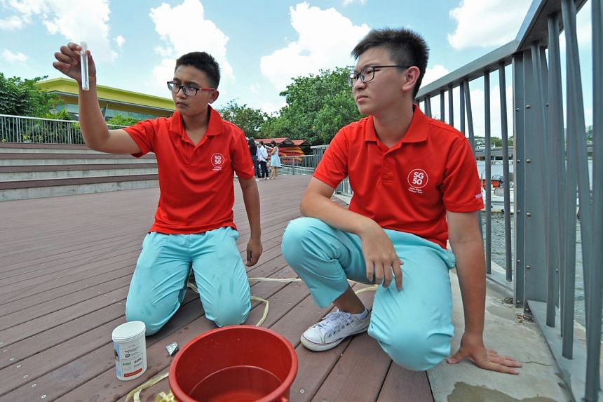 Pei Hwa Secondary students Idzhar Dandiar Bahtiar and Chee Kang Jie, both 15, testing a water sample from Punggol Reservoir for acidity and turbidity.