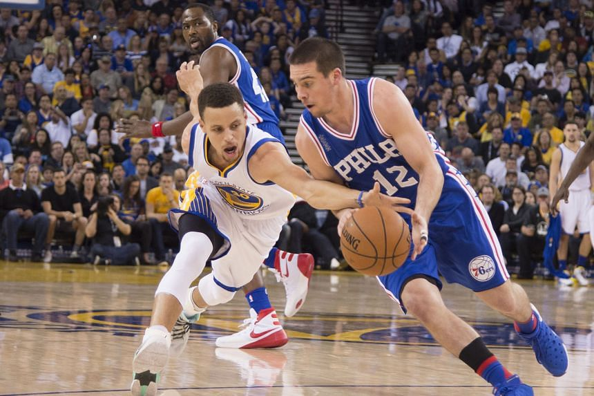 Golden State's Stephen Curry (left) reaching for the ball against Philadelphia's T.J. McConnell during the third quarter at Oracle Arena. The Warriors defeated the 76ers 117-105