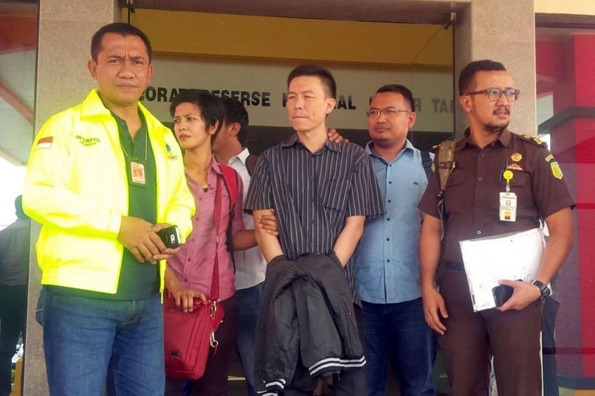 Lim (in black striped shirt) being escorted to Jakarta where he was handed over to a US Marshal yesterday.