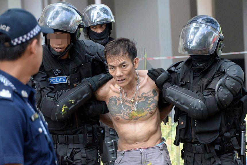 The suspected drug offender (left) being led away by police yesterday. The man trapped his mother in her bedroom of their flat (above) at Block 508, Ang Mo Kio Avenue 8, wielding a chopper and threatening to burn himself. Around 50 residents from the