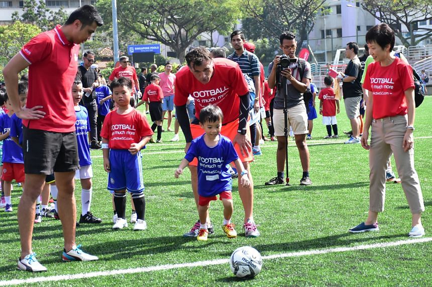 Former national goalkeeper Lionel Lewis (left), ActiveSG Football Academy principal Aleksandar Duric and Minister Grace Fu encouraging some of the 350 children who attended the launch of the programme yesterday.