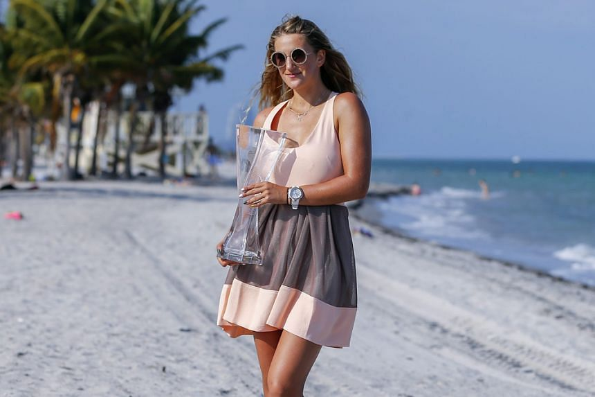 Victoria Azarenka poses with the Butch Buchholz trophy on the beach after defeating Svetlana Kuznetsova in the women's singles final at the Miami Open. The Belarussian's attention will now turn to extending her winning form to the coming clay-court t
