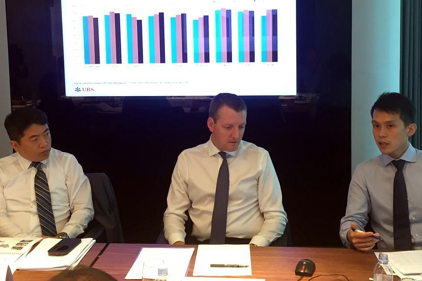 (From left) UBS Asset Management, Singapore head Michael Chin; Mr Mackie; and Mr Toh presenting the bank's report yesterday.
