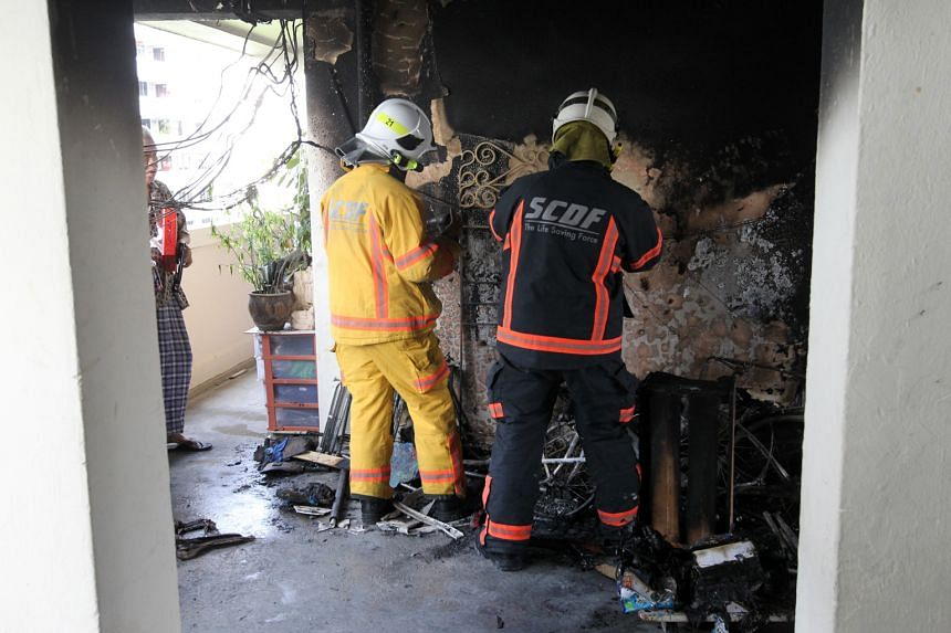 SCDF officers examining the scene of a fire that started outside an HDB flat on the seventh floor of Block 18, Eunos Crescent, yesterday. The blaze was put out by residents armed with buckets of water.