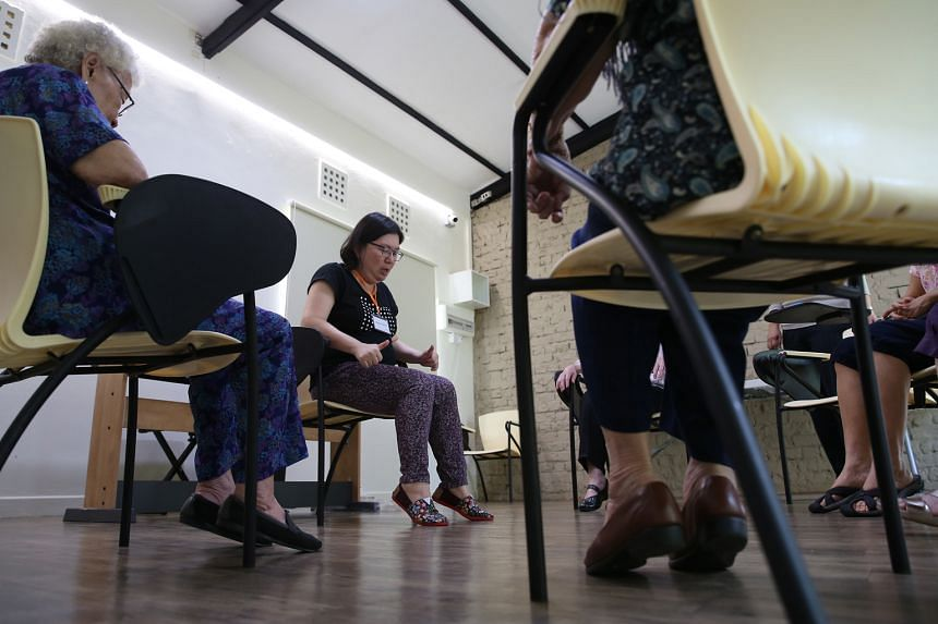 Activity facilitator Shirley Wong engaging dementia patients with light stretching and physical activities at the Montessori for Dementia Care centre. At the privately run centre, clients rise to the challenge of their abilities, said its director, D