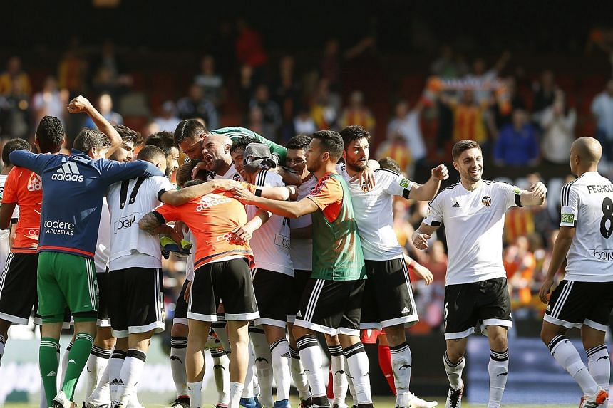 Valencia's players celebrate their dramatic 2-1 win under new coach Pako Ayestaran against Sevilla on Sunday. They are nine points clear of the relegation zone and will face Barcelona next.