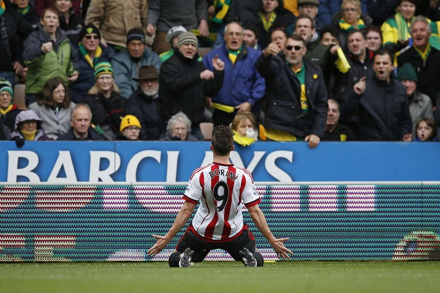 Sunderland striker Fabio Borini celebrates in front of the Norwich fans after scoring his side's opening goal from the penalty spot. The win allowed the Black Cats to go within one point of Norwich, with one game in hand.