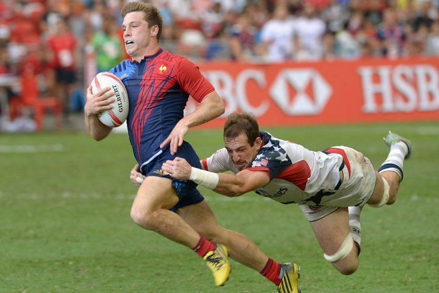 France's Stephen Parez (left) breaks away from the United States' Zack Test to score a vital try in their Singapore Rugby Sevens match at the National Stadium yesterday. France won the encounter 19-17.
