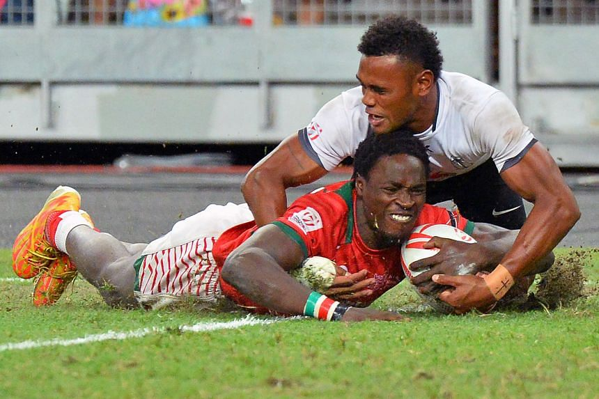 Left: It's wefie time for the victorious Kenyans, holding the trophy and wearing their gold medals. Below: Nelson Oyoo shaking off the challenge of Fiji's Amenoni Nasilasila to score Kenya's fifth try in their 30-7 pummelling of the series leaders in