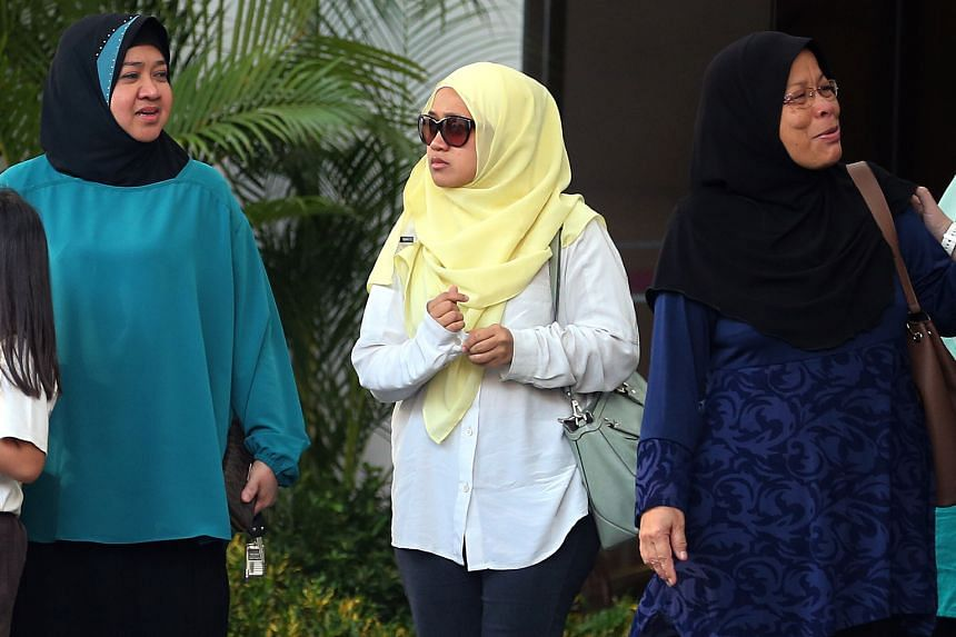 Ms Nurul Asyikin (centre) with family members outside the coroner's court yesterday. Her husband had second-degree burns on more than 80 per cent of his body.