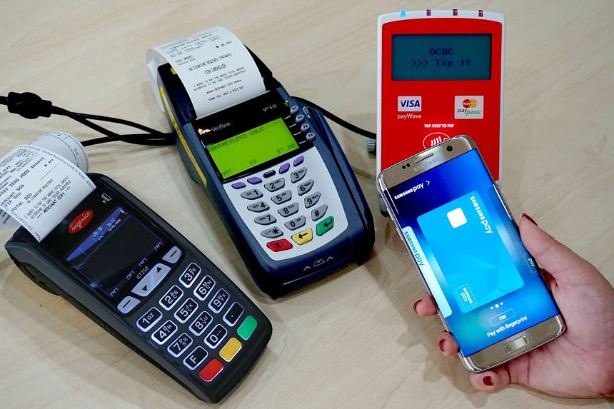 A Samsung Galaxy S7 edge being demonstrated with new near-field communication payment terminals (right and centre) and a traditional magnetic-stripe terminal (left). Samsung Pay works with both types of terminals.
