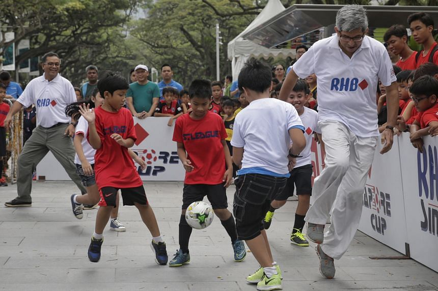 Minister for Communications and Information Dr Yaacob Ibrahim (right) and Football Association of Singapore president Zainudin Nordin (left) joined participants for a five-a-side kickabout as part of a curtain-raiser to the RHB Singapore Cup Kids' To