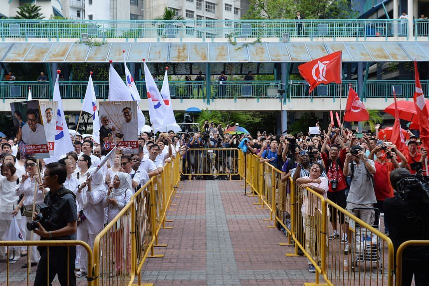 Veteran opposition figure Kwan Yue Keng at Keming Primary School. He said he would contest only if Dr Chee was disqualified. PAP supporters in white and SDP supporters in red gathering at the Keming Primary School yard yesterday. When nominations for