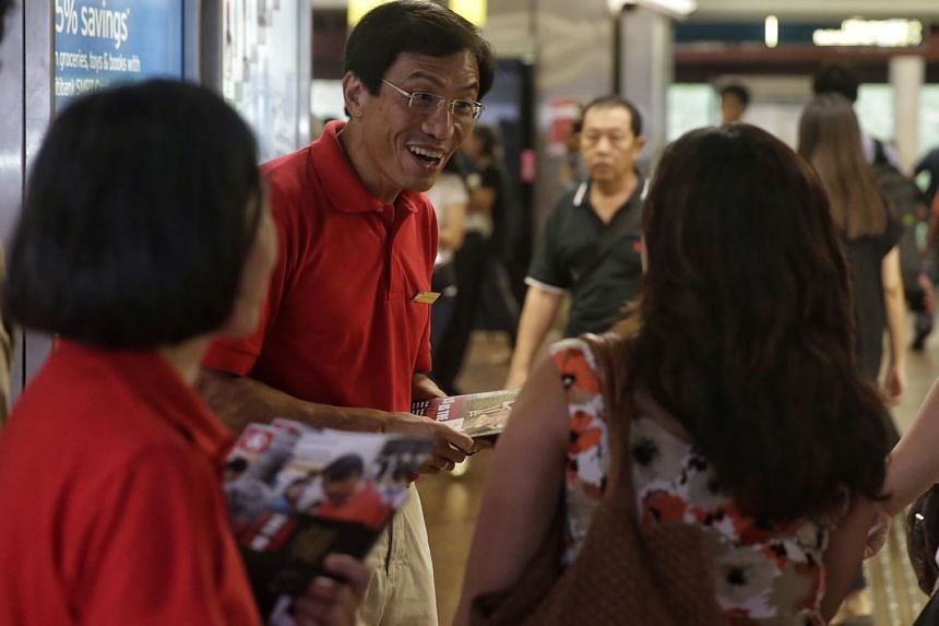 SDP chief Chee Soon Juan giving out fliers at Bukit Batok MRT Station yesterday. He said the party will spell out how it plans to ensure a smooth takeover of the town council should he win the Bukit Batok by-election.