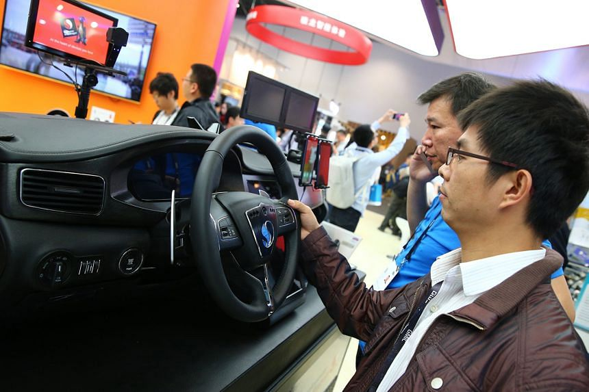 A visitor tries out the Connected Car Solutions System at the Qualcomm exhibition booth at the 2016 Global Mobile Internet Conference in Beijing this month.