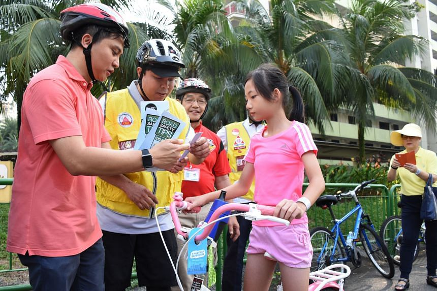 Mr Supaat (left), an MP for Bishan-Toa Payoh GRC, with Active Mobility Patrol members (in yellow vests) and another volunteer reaching out to a cyclist about road safety.