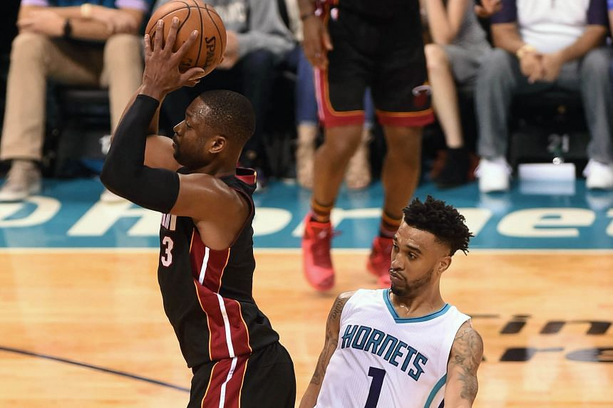 Miami Heat guard Dwyane Wade shrugs off the attentions of Charlotte Hornets guard Courtney Lee to shoot during the second half in Game 6 at the Time Warner Cable Arena. The Heat won 97-90 to take the series to a Game 7 decider in Miami.
