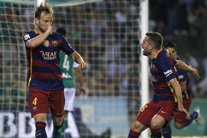 Barcelona's Ivan Rakitic (left) celebrates with Jordi Alba after scoring the opening goal against Real Betis five minutes into the second half. Barca won 2-0 to stay at the top of the La Liga table on 85 points.