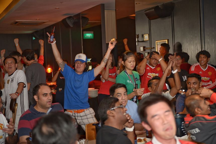 Foxes fan Parry Tan (in blue) reacting to Leicester skipper Wes Morgan's equaliser against Manchester United at Harry's at Boat Quay. He was the most vocal fan yesterday, even though he was outnumbered by United supporters.