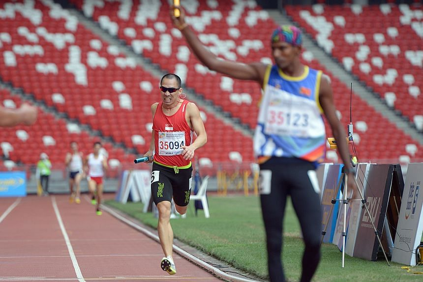 Lien Choong Luen, in red, brings Singapore a silver medal in the 4x400m relay for men over 35 in the final event of the Asia Masters Athletics Championships yesterday.