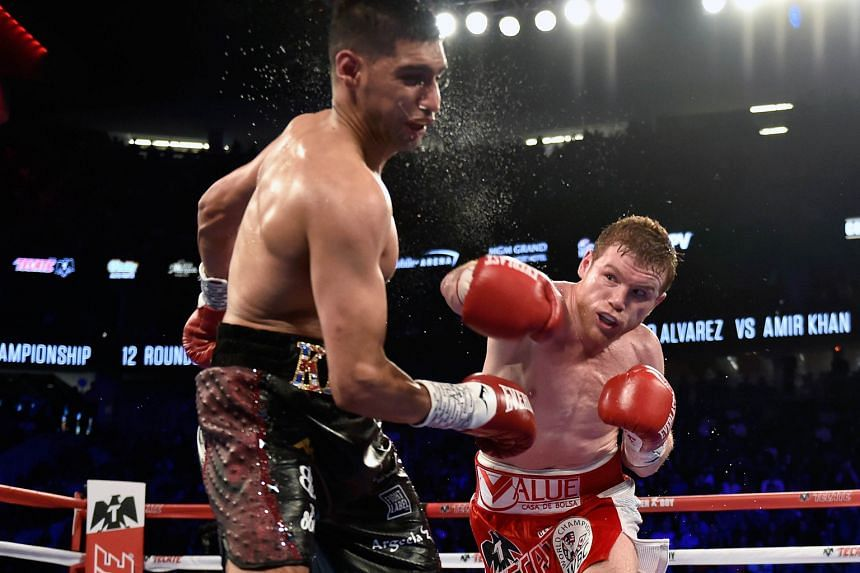 """British boxer Amir Khan (left) is knocked out by Saul """"Canelo"""" Alvarez of Mexico during their WBC middleweight title fight in Las Vegas on Saturday."""