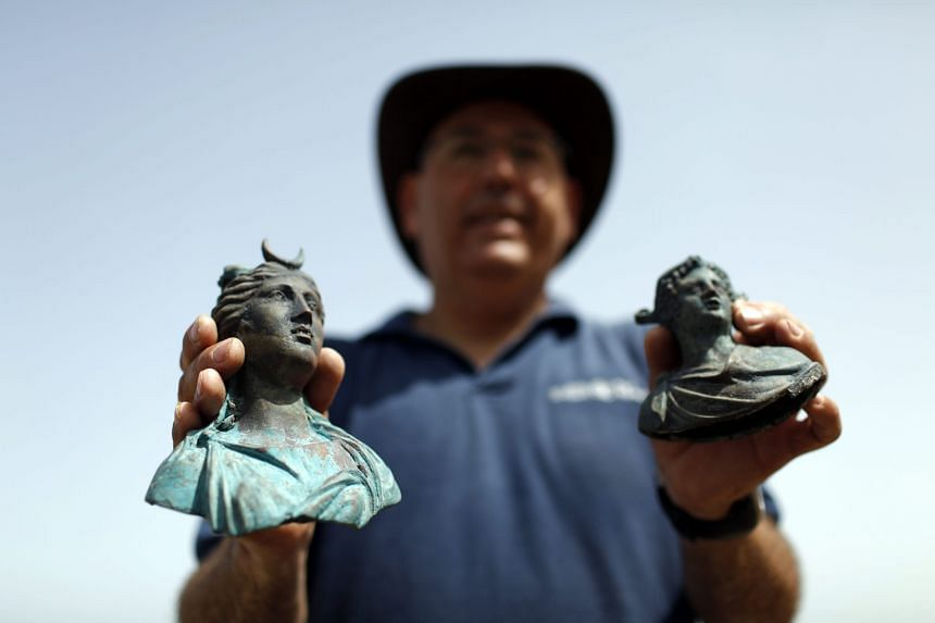 Dr Jacob Sharvit, the director of the Marine Archaeology Unit of the Israel Antiquities Authority, yesterday showing two of the archeological finds at the ancient port of Caesarea, Israel. Israeli divers found an ancient marine cargo in a merchant sh