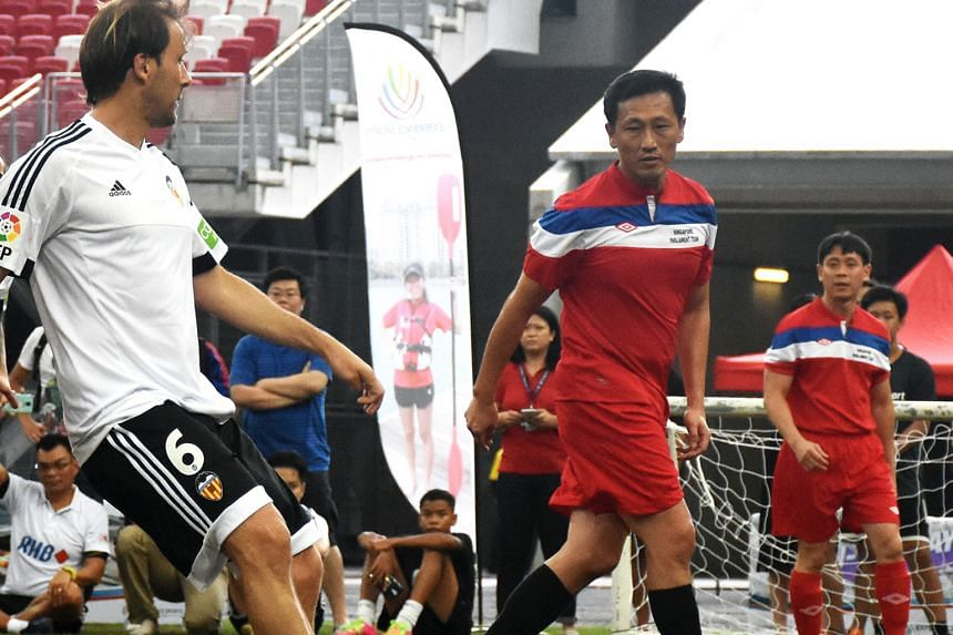 Spanish La Liga ambassador and former Valencia player Gaizka Mendieta (left) releasing a pass under the attention of Acting Minister for Education Ong Ye Kung (black socks) in an exhibition match at the Football With A Heart tournament yesterday. Org