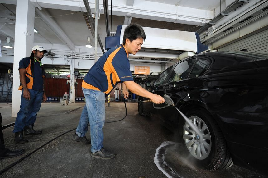 Mr Tan, managing director of car grooming firm Groomwerkz, showing how his company uses de-ionised water to wash cars. Home-grown water treatment firm De.Mem has been treating water to make it de-ionised for Groomwerkz's car wash services, making car