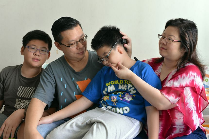 Benjamin (centre) with his parents showing the Baha Attract, a new hearing aid that uses a magnet embedded under the skin instead of a screw to hold the sound processor in place.