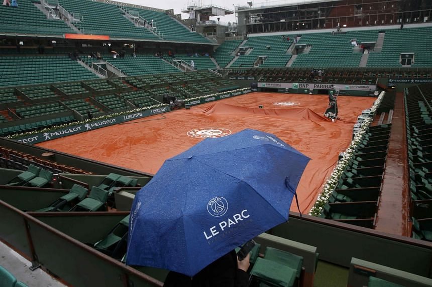 A sole umbrella-wielding spectator waiting in hope while the covers remain on the surface of the main Philippe Chatrier Court yesterday. The organisers of the French Open plan to introduce a roof to the main court, but that will not happen until 2020