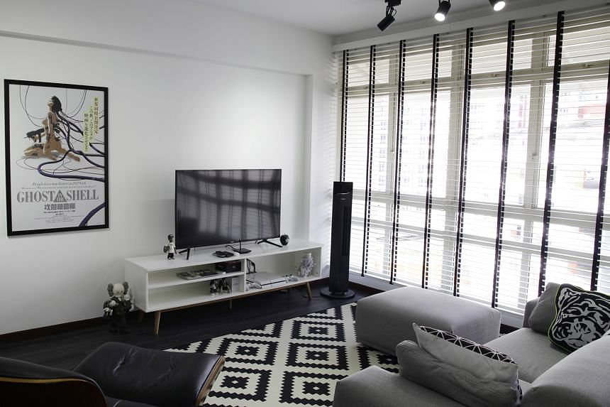 The black-and-white palette in the living room (above) of the five-room HDB flat in Sengkang extends into the bedroom (below). The white DJ console in the living room of Mr Christopher Kurt Loy (above) has been custom-made to hide its cables.