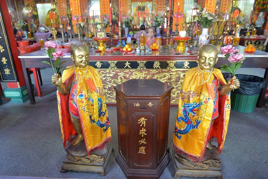 Devotees in the main prayer hall of the Tang Gah Beo temple are greeted by stone deity statues painted in gold (above) at the entrance.