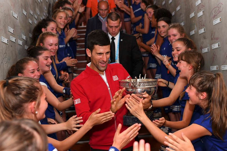 Novak Djokovic celebrating his French Open win with ball girls. The world No. 1 has set his sights on becoming only the third man to capture a calendar-year Grand Slam.
