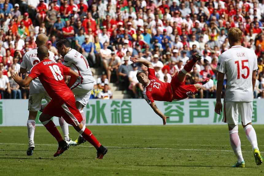 Switzerland's Xherdan Shaqiri (right) scoring a spectacular overhead kick in their Euro 2016 last-16 tie against Poland yesterday. His 82nd-minute goal cancelled out Jakub Blaszczykowski's 39th-minute opener, and the tie went into extra time and then