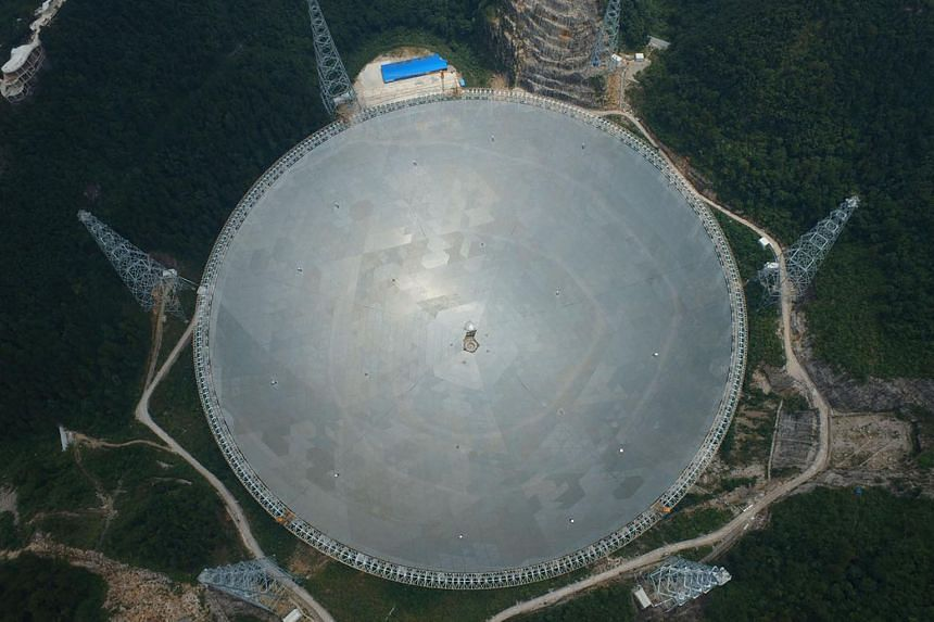 China's 500m aperture spherical telescope, named Fast, pictured at three different assembly stages in Pingtang County, south-west Guizhou province. The topmost photo was taken in August last year, the second in December, and the third on Wednesday. F
