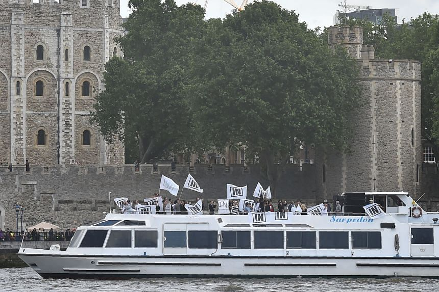 """Stay: A boat carrying supporters of the IN campaign to remain in the EU sailing past the Tower of London on the River Thames on June 15. Leave: A boat decorated with flags and banners from a group campaigning for a """"leave"""" vote in the EU referendum s"""