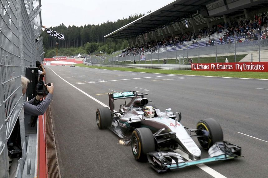 Britain's Lewis Hamilton takes the chequered flag to win the Austrian Grand Prix yesterday, cutting Nico Rosberg's lead to just 11 points. The German sustained damage in their last-lap clash and finished fourth.