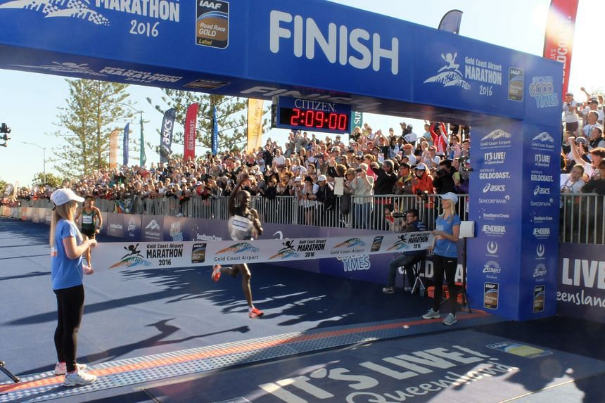 Kenneth Mungara raising his hand as he breasted the tape ahead of Japan's Yuki Kawauchi at the Gold Coast Airport Marathon yesterday.