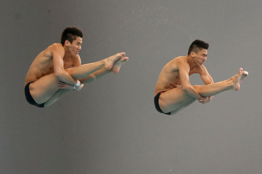 Twins Mark (left) and Timothy Lee on their way to winning gold in the Fina open men's 3m synchronised category yesterday at the National Diving Championships at the OCBC Aquatic Centre.