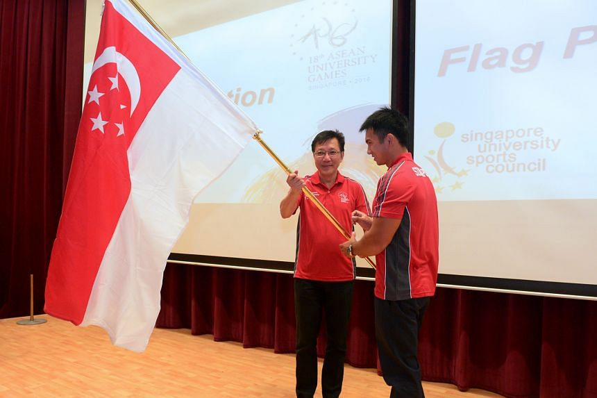 Associate Professor Tan Teck Koon (left), head of the Singapore delegation for the Asean University Games, presenting the Republic's flag to canoeist Mervyn Toh at University Town, the National University of Singapore, yesterday. The Singapore contin