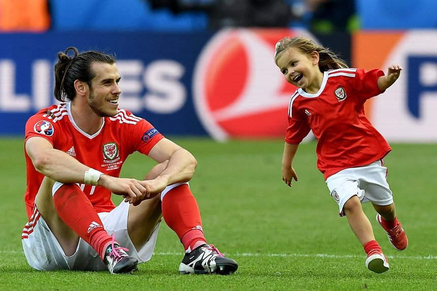Gareth Bale of Wales enjoying his time with his daughter after the 1-0 round-of-16 victory over Northern Ireland on June 26.