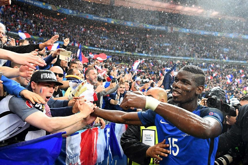 Joyous fans celebrating in the rain with midfielder Paul Pogba, after France beat Iceland 5-2 in their Euro 2016 quarter-final at the Stade de France. The Juventus player netted the hosts' second goal.