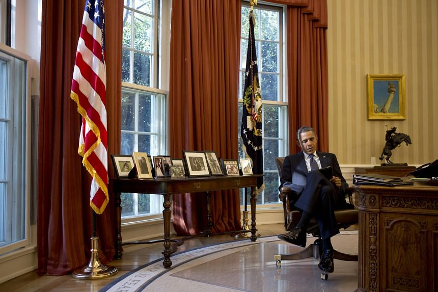 Mr Obama in the Oval Office, the official office of the US President, in 2012. Come nightfall, he retreats to the Treaty Room down the hall from his bedroom on the second floor of the White House residence.