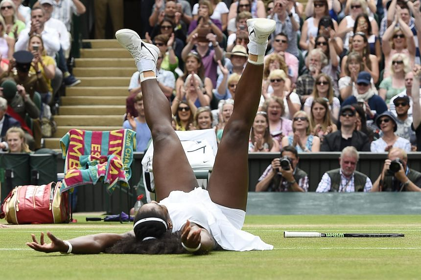 Overwhelmed by her victory, Serena Williams falls to the grass after winning 7-5, 6-3 against Angelique Kerber in the Wimbledon women's singles final.