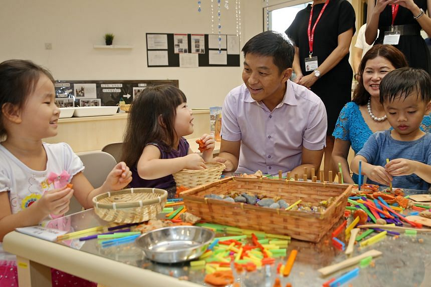 Minister for Social and Family Development Tan Chuan-Jin at the new E-Bridge Pre-School yesterday. With him are pre-schoolers (from left) Wang Yunhan, four; Tan Le En Eryn, three; and Jovan Pang; three.