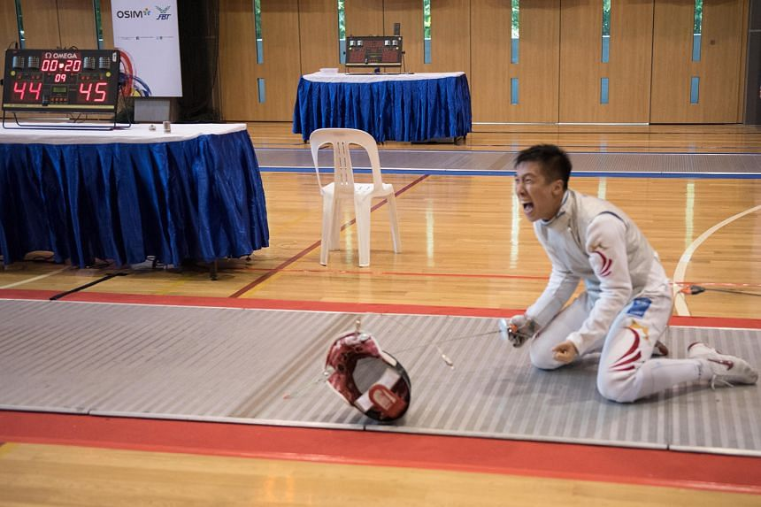 Singapore's Zhang Zhenggang after winning the last point of the closely fought men's foil team final to seal a 45-44 win for the gold medal.